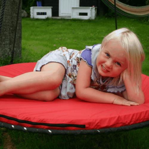 Pige ligger på en rød pude