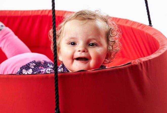 Baby ligger i en Sansegynge med en rød kant