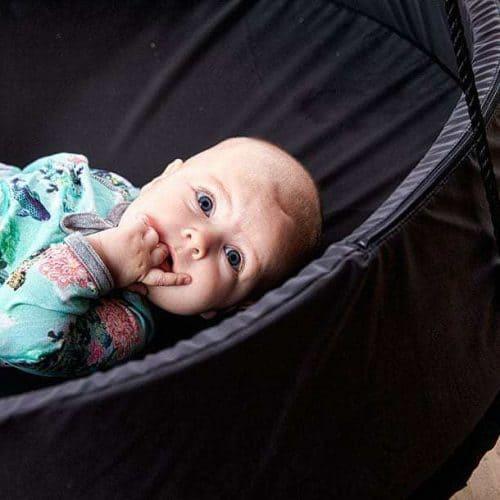 Baby ligger i en Sort Sansegynge med en sort kant