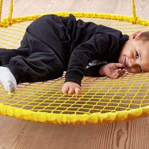 Barn ligger i en gul sansegynge