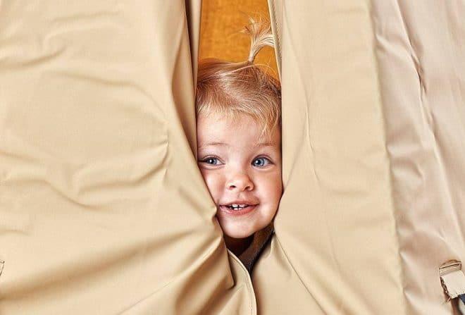 Barn kigger ud af et sandfarvet telt