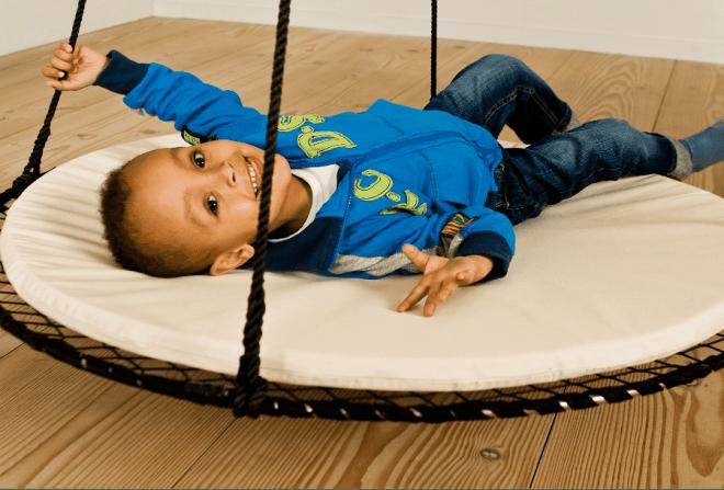 Barn ligger i en sort sansegynge med hvid pude