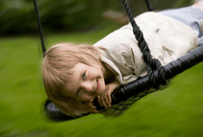 Barn der leger på en sort udendørs Sansegynge
