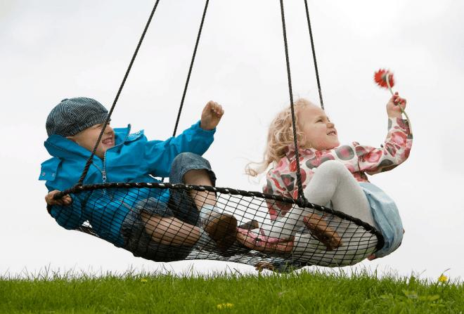 Børn leger i en sort sansegynge