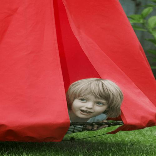 Pige kigger ud fra en Sansegynge med et rødt telt